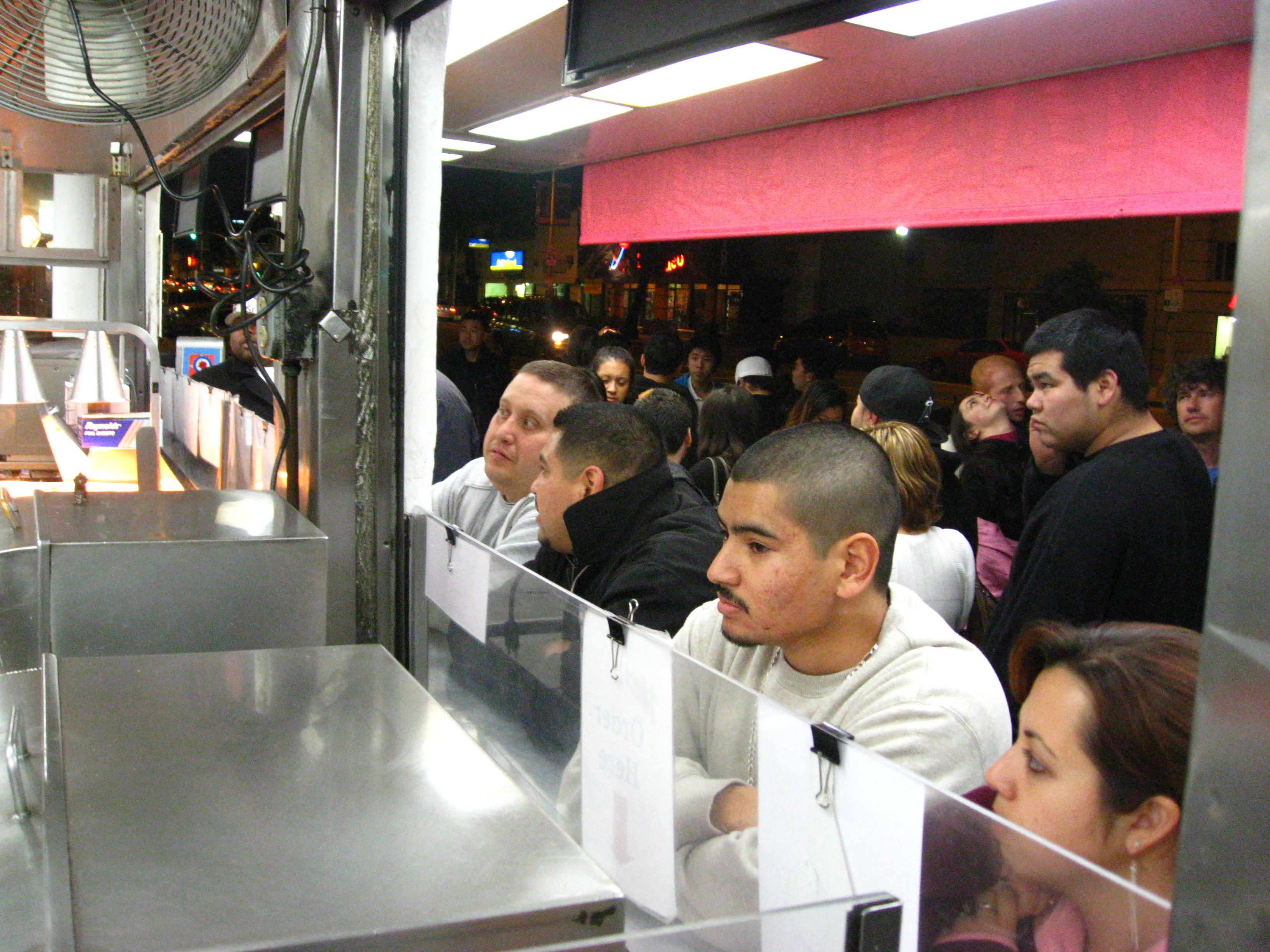 The line is four rows deep. The crowd is quite mixed, everyone loves hot dogs at midnight.