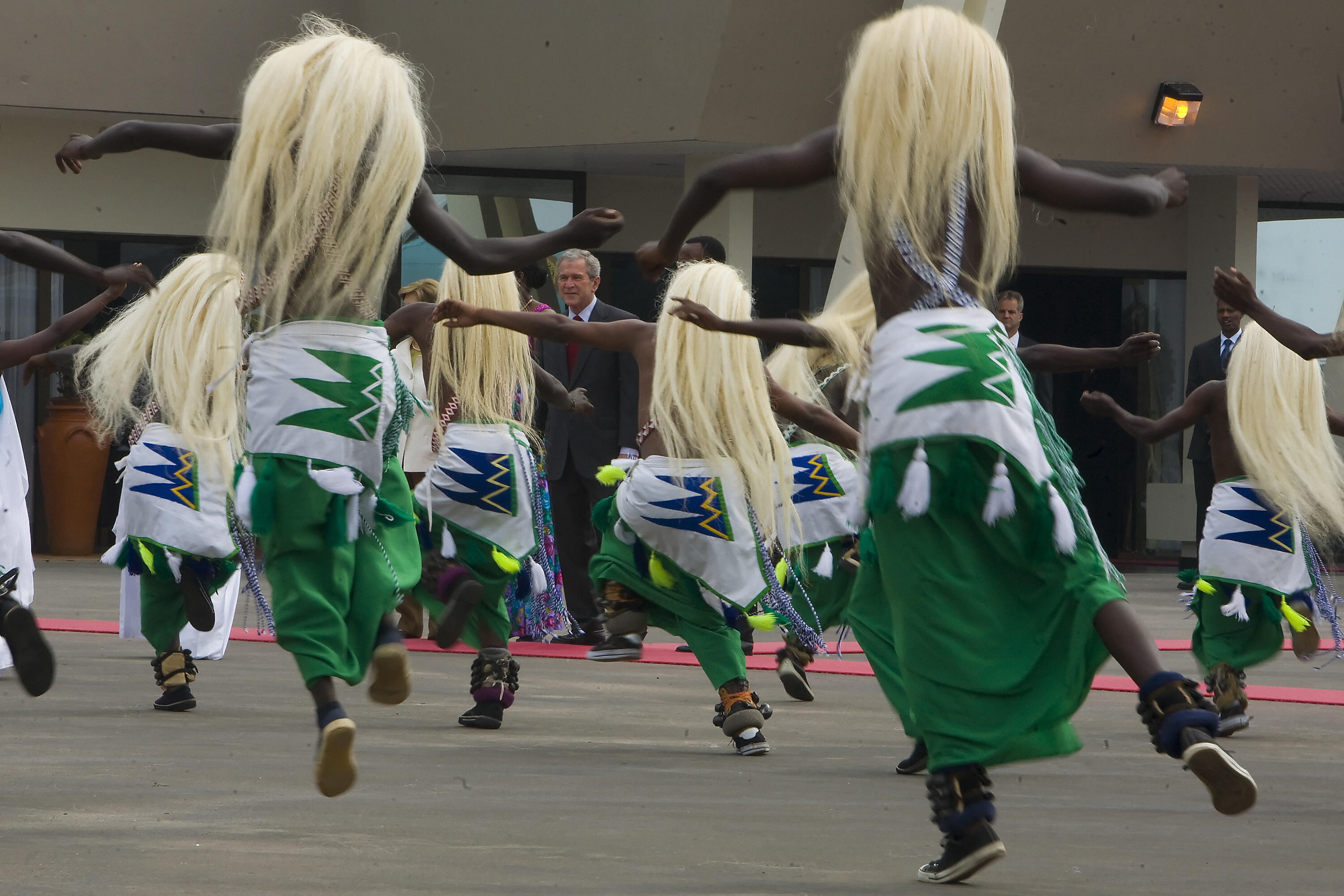 Dancers greet Bush when he arrives at the airport in Rwanda.