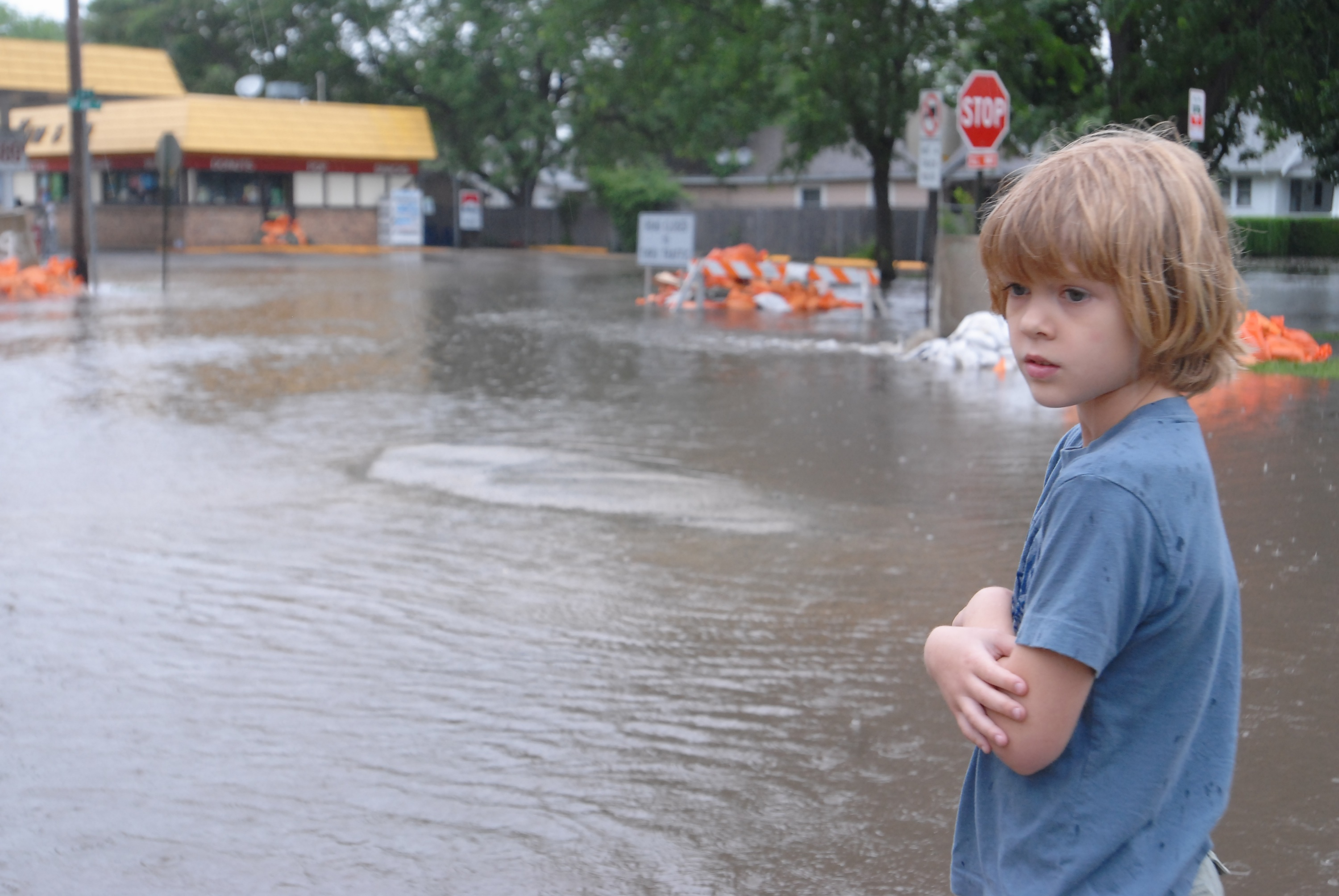 Eight year old Sammy Petersen watches as rising water inundates the low lying area of the Czech Village.