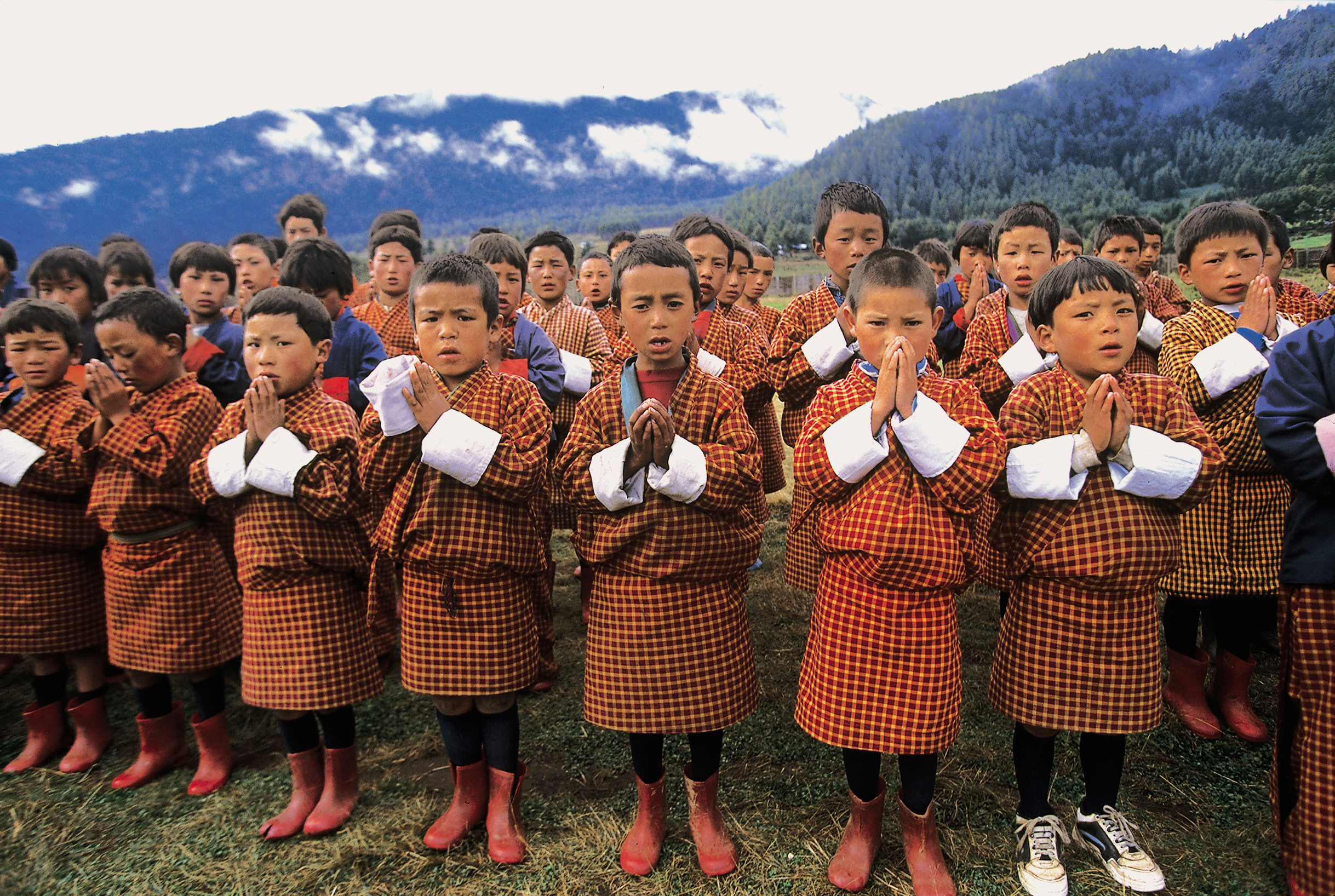 Schoolchildren performing morning prayers at school assembly in Bhutan.