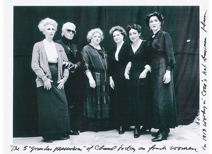 Karl Lagerfeld with Chanel seamstresses costumed as women working in Chanel's hat business in 1913.