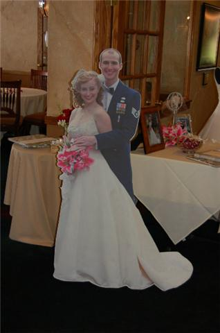 "I didn't want to wear my wedding dress to the reception, but lots of people had wanted to see ""a life size me"" in it- so my parents made a cardboard cutout of my husband and me on our wedding day. Hilarious!"