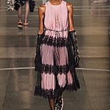 Picture her in this exact look, sans elbow-length leather gloves. We think this pink midi, complete with a gauzy overlay, would fit right into the elegant side of Michelle's wardrobe. Christopher Kane Spring 2017.