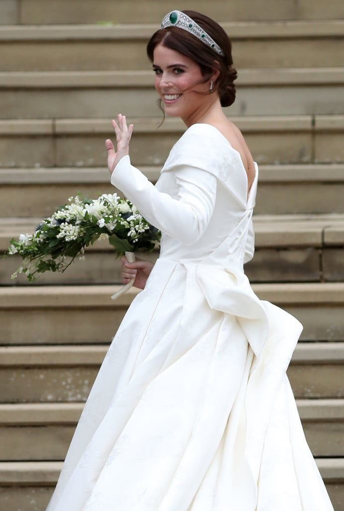 Princess Eugenie and Jack Brooksbank are married! After months of speculation, we finally got to see what Eugenie's wedding gown looked like, as well as who she entrusted with the task of creating the most important outfit of her life — and, well, it certainly didn't disappoint. For her big day, the princess wore a regal gown by British designer Peter Pilotto with a pair of Charlotte Olympia heels. With a modern and feminine silhouette, Eugenie's dress looked exactly like what we had imagined. She accessorised it with Greville Emerald Kokoshnik Tiara — which was lent to her by the queen — as well as diamond and emerald drop earrings, but surprised everyone by choosing not to wear a veil. Read on to see Princess Eugenie's dress in more detail.