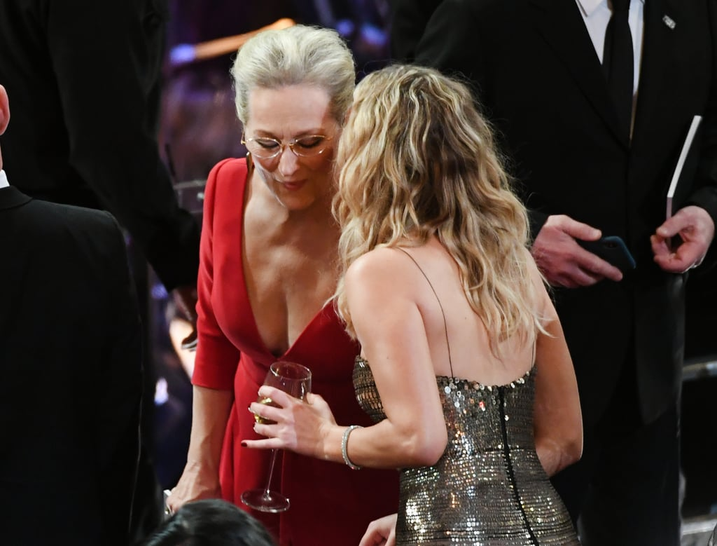 Meryl Streep was stopped by Jennifer Lawrence (wine still in hand) for a chat.