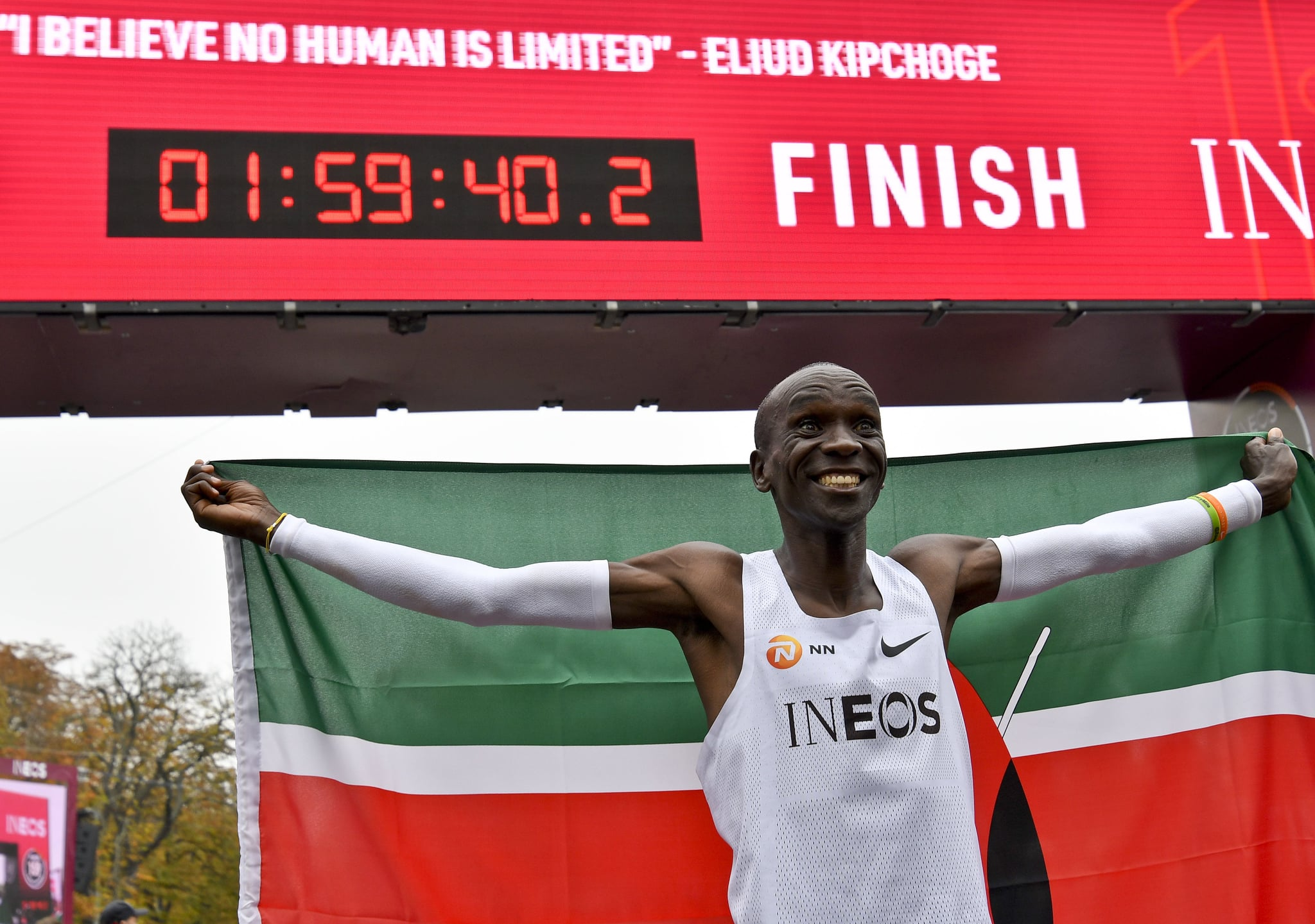 TOPSHOT - Kenya's Eliud Kipchoge (white jersey) celebrates after busting the mythical two-hour barrier for the marathon on October 12 2019 in Vienna. - Kipchoge holds the men's world record for the distance with a time of 2hr 01min 39sec, which he set in the flat Berlin marathon on September 16, 2018.He tried in May 2017 to break the two-hour barrier, running on the Monza National Autodrome racing circuit in Italy, failing narrowly in 2hr 00min 25sec. (Photo by HERBERT NEUBAUER / APA / AFP) / Austria OUT (Photo by HERBERT NEUBAUER/APA/AFP via Getty Images)