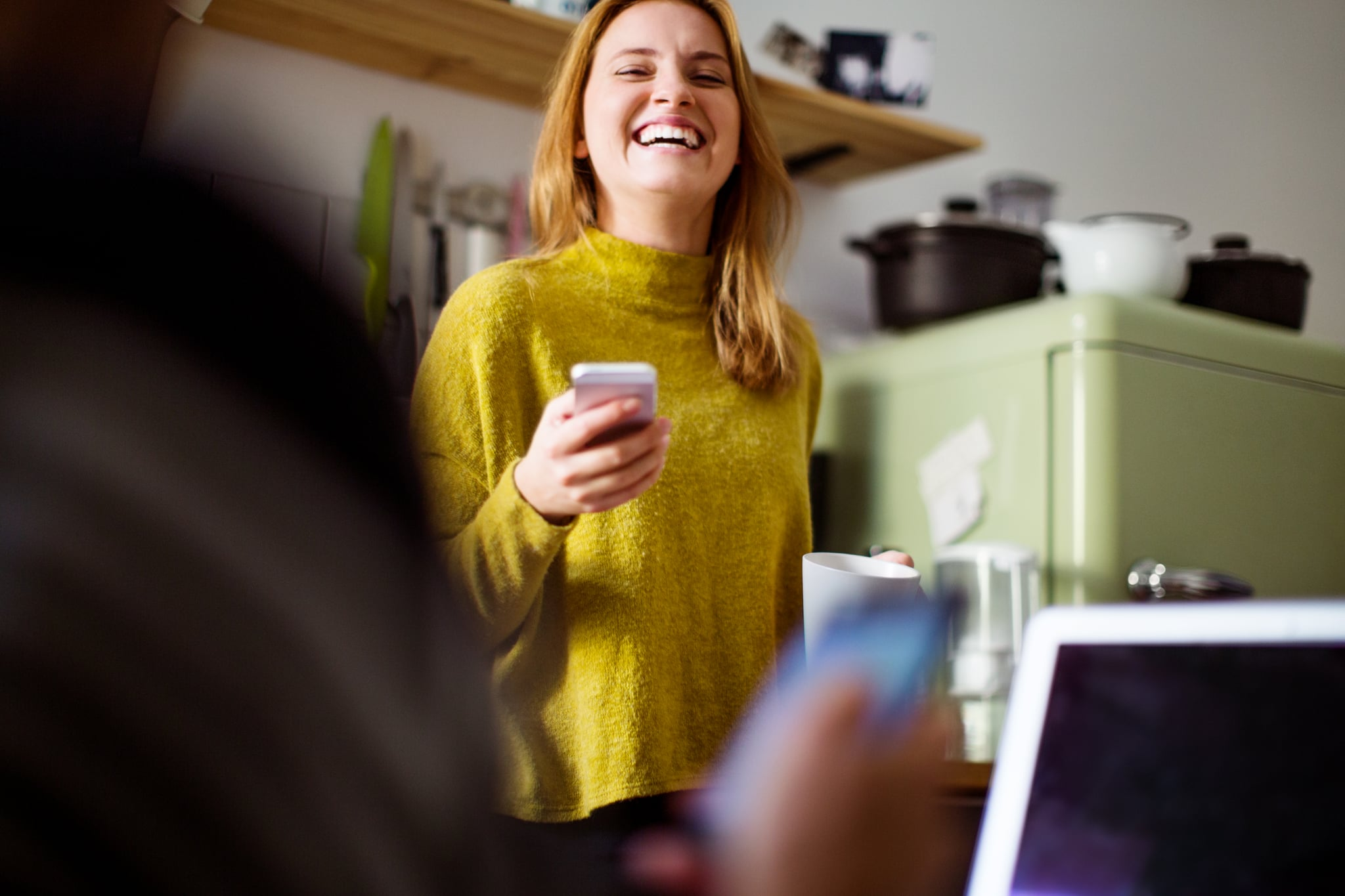 Young woman talking to man sitting in front and smiling. Cheerful female with mobile phone in kitchen.