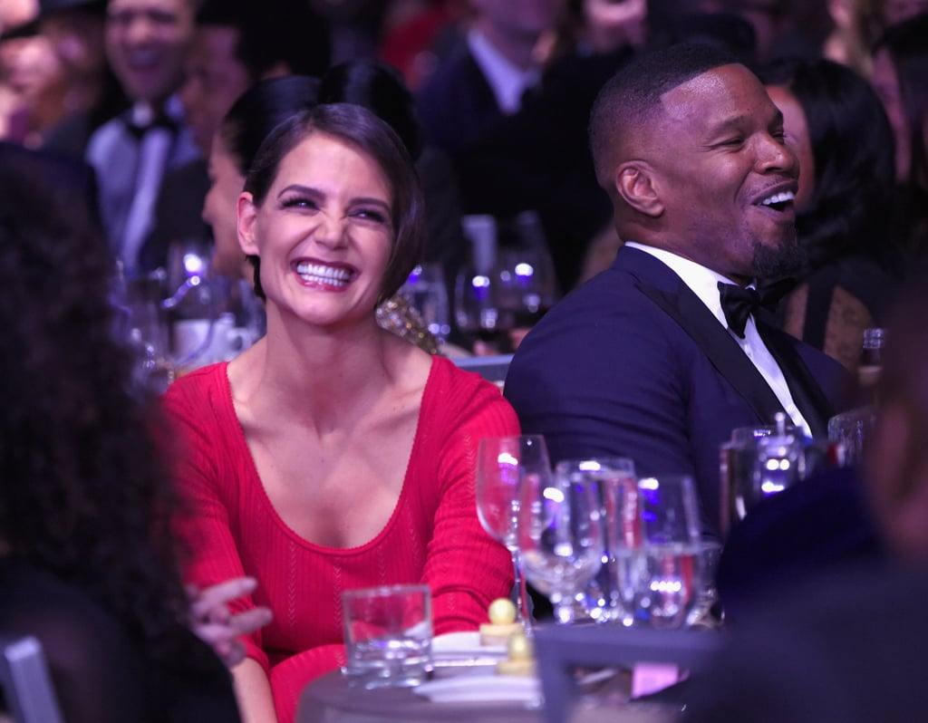 "Jamie Foxx and Katie Holmes are coming out of hiding. The notoriously private couple made a rare appearance together at Clive Davis's annual pre-Grammys bash in NYC on Saturday night. Clive reportedly ""gave them a hard time"" from the stage when Jamie and Katie opted not to sit next to each other at first. Later, they switched seats and were spotted side by side staring lovingly at one another, Katie whispering into Jamie's ear. The pair, who were first linked back in 2013, were all smiles throughout the evening. This marks their first official outing after the two were photographed holding hands on the beach in September. Katie also popped up at Jamie's 50th birthday bash and supported him at his Prive Revaux eyewear store opening in December. Read on to see more photos from Jamie and Katie's sweet night out."