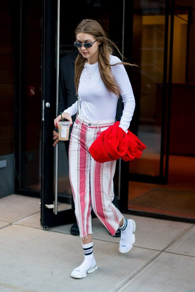 باعتبارها واحدة من عارضات الأزياء الأكثر شهرةً في العالم، فإنّ جيجي حديد دائمة التنقّل حقيقةً. لذا سيساعدها كثيراً اختيار أحذية مريحة لقدميها حتماً. إذ أطلّت العارضة البالغة من العمر 23 عاماً هذه مؤخراً في شوارع مدينة نيويورك مرتديةً قميصاً أبيضاً طويل الأكمام، وبنطالاً مقلّماً، وحذاء سنيكرز يوحي بأنّها جوارب ذات نِعال إلى حدٍّ ما. وجاءت تلك الأحذية المريحة كثمرة للتعاون الأخير بين علامتي فينتيمينتس وريبوك البارزتين. كما تجمع جيجي وريبوك شراكة مستمرّة منذ عدة سنوات، لذا فكثيراً ما نراها ترتدي ملابس رياضيّة من هذه العلامة التجاريّة تحديداً. شاهدي أدناه صوراً لأروع قطع أزياء موضة الشارع التي أطلّت بها العارضة اللّامعة تلك، ثمّ اشتري أحذية سنيكرز مُماثلة على نمط نِعال الجوارب – إلى جانب الزوج الباهظ الذي ارتدته جيجي.