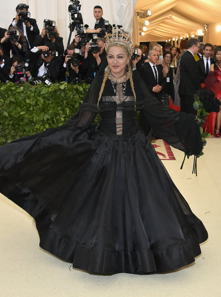 "At the Met Gala on Monday night, it seemed like the event's lucky guests interpreted the theme in one of three ways: bright colors and shades of gold, pure white, or all-black everything. Madonna opted for the latter, arriving on the red carpet in a voluminous black gown that was the perfect blend of high fashion and goth prom queen (translation: she might cast a spell on you if you step on her train, but at least it'll be with a designer spell book). She topped off the daring look with a bouquet of black roses, a fishnet veil, and a glittering white and gold crown decked out with numerous crosses to keep with the night's official theme: ""Heavenly Bodies: Fashion and the Catholic Imagination."" See more photos of her ensemble below!"