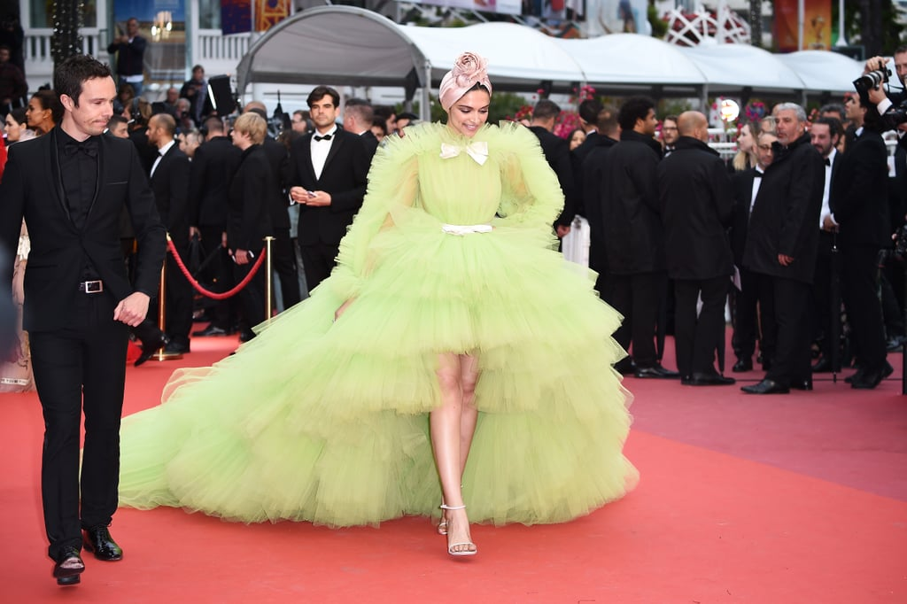 "In case you haven't heard already, Deepika Padukone dominated the Cannes Film Festival red carpet this year. All eyes were on the 33-year-old Bollywood actress as she consistently stunned onlookers with her daring and dramatic style. She delivered a major moment earlier in the week wearing a voluminous Dundas gown and then performed a total ""fashion mic drop"" with her neon tulle gown at the Pain and Glory premiere on May 28. Her ginormous Giambattista Valli Couture gown is a callback to Jennifer Lopez's hot-pink premiere dress last year, but, of course, Deepika added her own twist to this already-wild look. Her gown featured long ruffled sleeves, as well as a bow at the collar and a belted waist. She paired the gown (and its gorgeous train) with neutral Stuart Weitzman heels, Lorraine Schwartz jewelry, and a pink Emily London headdress. Ahead, see more glimpses of Deepika's look from all angles — your favorite highlighter could never. Related: Indian Icon Deepika Padukone Looked Straight From the Heavens at the Met Gala"