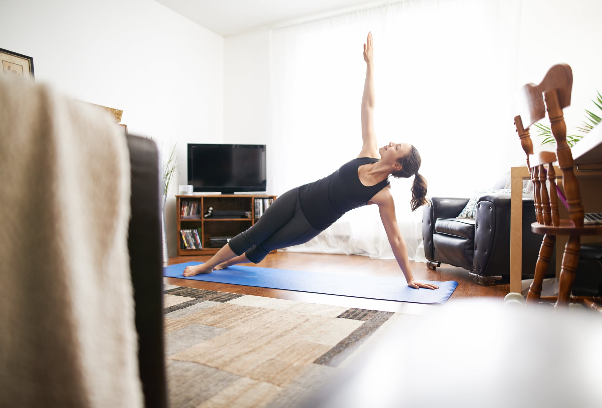 Full length shot of a young woman practicing yoga at home