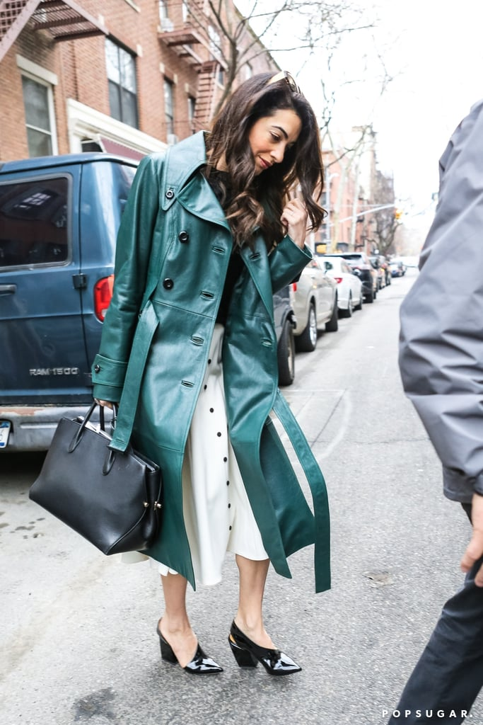 """Hands down, Amal Clooney has the best collection of coats we've seen for Spring. After debuting this leather and twill mashup by Alexander Wang, she was spotted in an Ermanno Scervino leopard coat. At the time, you probably thought, """"wow, this one is the coolest,"""" but honestly, you hadn't seen anything yet. Amal wasn't done. On April 3, as she went on her way to Columbia University in NYC, Amal was spotted in a green leather trench from the Fall '18 Michael Kors Collection. The straps on the double-breasted style were left untied to reveal a black sweater and white buttoned skirt.  Amal accessorized with a smart-looking black bag, ZANZAN sunglasses, and a pair of block pumps. Her whole ensemble was sophisticated for sure; perhaps she was about to give an in-class lecture? There's no denying this human rights lawyer and activist has enough work wear inspiration to last an entire semester (or more). Read on to see Amal's latest coat, then shop similar polished pieces.      Related:                                                                                                           Amal Clooney's Best Dresses Were Pulled From the Archives"""