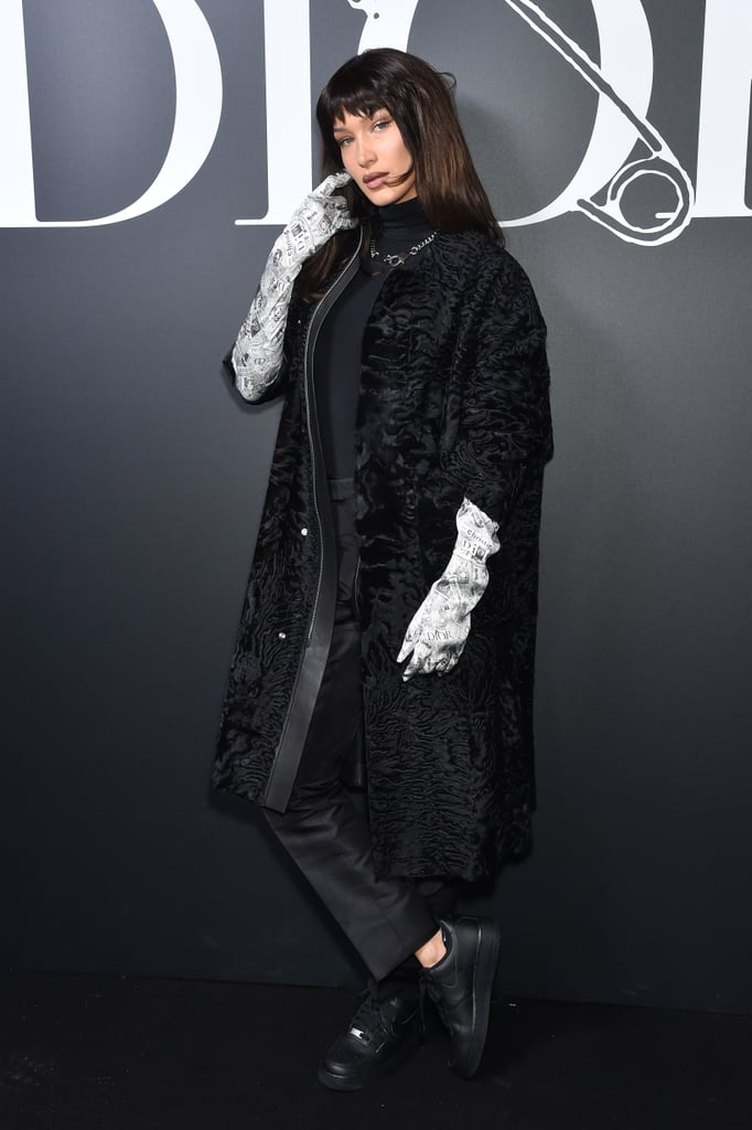 Cruela de Vil has finally met her fashion match in the form of Bella Hadid's stylish outfit at Paris Fashion Week. While attending the Dior Homme Menswear Fall/Winter 2020-2021 show on Friday, Bella rocked a ruched Christian Dior black coat over a matching turtleneck and fitted trousers — and something tells me the 101 dalmatians would be shaking because of how stylish she looks. Yes, Cruella is a villain, but the only thing villainous about this look is that Bella's newspaper print gloves probably cost more than my monthly rent. She also paired the look with a silver chain-link necklace and a pair of Nike low top sneakers. Keep scrolling to take a closer look at Bella's wickedly cool outfit from all angles ahead.