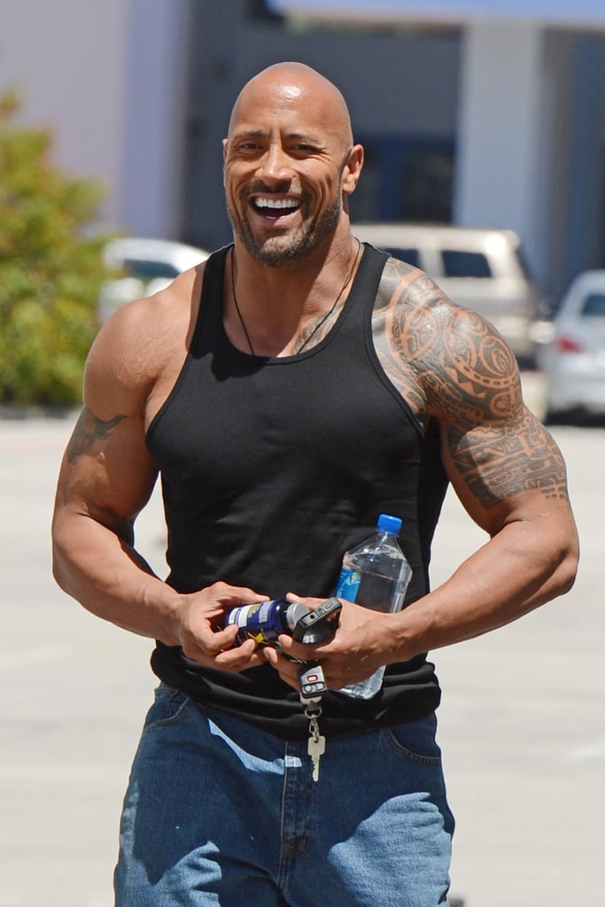 It's not hard to tell why Dwayne Johnson was named the Sexiest Man Alive in 2016. When the devoted family man and charismatic actor isn't making us melt on screen, he's heating things up in the gym, on the red carpet, on a plane, in a parking lot, etc. While we certainly have a soft spot for The Rock's hard-core abs, he really gets us hot and bothered when he's wearing a formfitting shirt. Whether he's trying to make us weak in the knees on purpose or he simply made a mistake and bought an XXS, we certainly aren't complaining when he slips into tight tees or tank tops to show off his bulging biceps.
