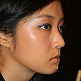 """Laura Mercier key makeup artist Talia Shobrook used three different products to create the teal cat eye. First, she applied the brand's Eye Pencil in Midnight Bleu ($20) and then topped it with Kohl Eye Pencil in Black Turquoise ($20). Finally, she pressed in Baked Eye Colour in Lagoon ($22), a bold turquoise. """"I wanted the eyes to look like jewels and the skin to be balmy and dewy, because Vegas is in the desert,"""" Shobrook said."""