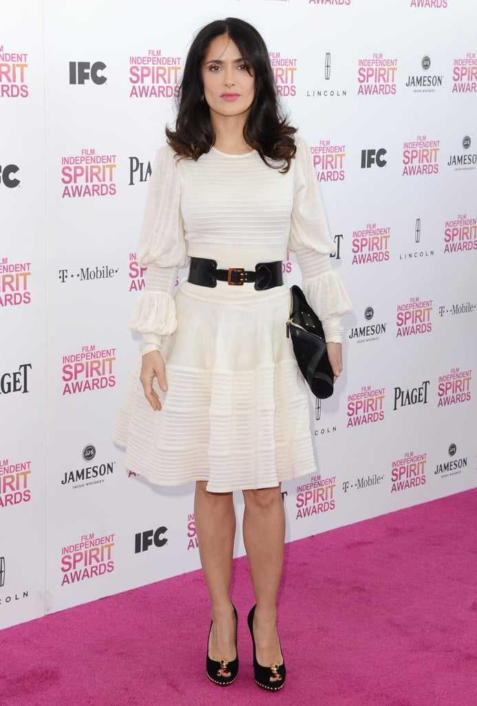 Salma Hayek contrasted her Alexander McQueen LWD with a bold black waist belt, a larger black clutch, and black peep-toe pumps.