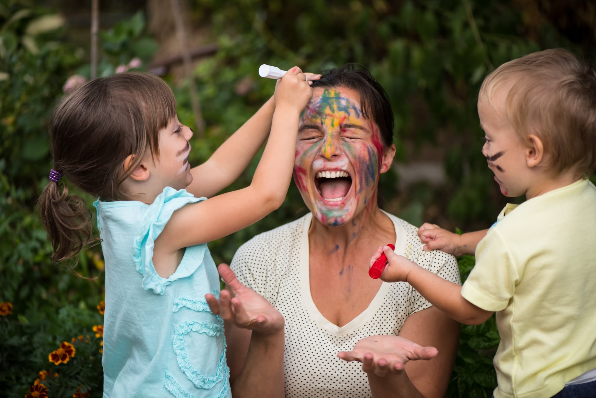 Children are painting mother's face with body colours outside - mother got beyond happiness level from playing with kids