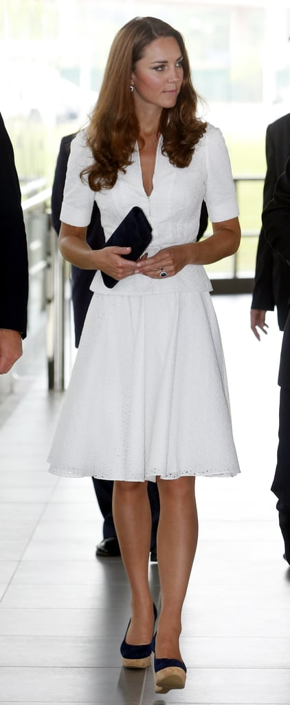 Midday, the brunette beauty stunned in a crisp white Alexander McQueen skirtsuit and navy blue Stuart Weitzman wedges. This isn't the first time Kate has worn a McQueen skirtsuit — she actually wore an ivory-hued version for the kickoff of Diamond Jubilee celebrations earlier this year.