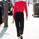 Understated and still cool, Gigi wore a namesake knit and a matching red frames.