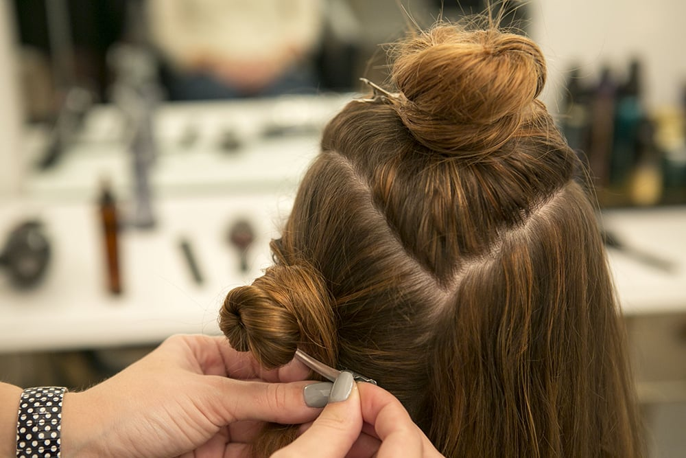The top section can be twisted on top of your head, and then twist one of the side sections, only leaving one section out. Because your hair is mostly dry, you can work in bigger sections, like Halpin did. Source: Caroline Voagen Nelson