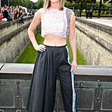 Jennifer Lawrence bared her toned midriff in a daring Dior design for the Dior Haute Couture show. She paired a pastel, metallic crop top with charcoal wool pants, sunglasses, black pumps, and a Bois de Rose bracelet, all by Dior.