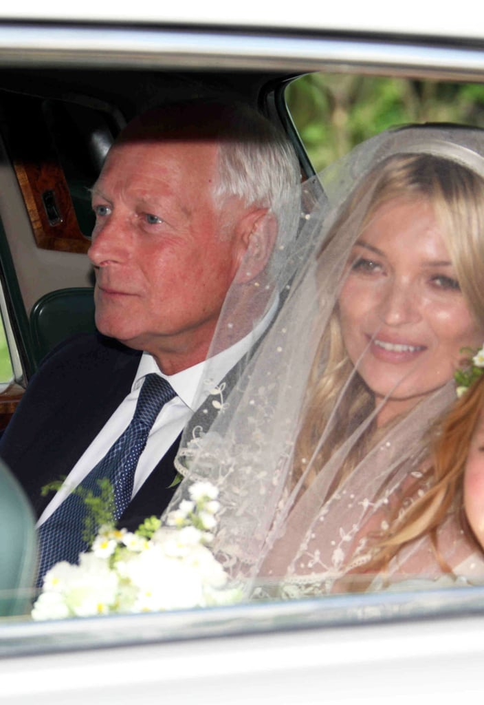 Kate Moss beamed this afternoon on her way to marry Jamie Hince at a church in Southrop, England! The happy couple posed outside St. Peter's last night after they finalized the details of their vow exchange, which happened at 3:30 p.m. (GMT). Kate was decked out in a veil and a John Galliano gown as she rode to the ceremony with family. Manolo Blahnik had the honor of designing her shoes, which featured a blue lining! Kate's maid of honor, pal Trish Simonon, will be by her side in a creation from Erdem. Jamie is also set to have a best woman, his bandmate from The Kills Alison Mosshart. Both Alison and Jamie were to be decked out in Yves St. Laurent. This is just the beginning of what's supposed to be a three-day bash for Jamie and Kate's family and friends. The tents are ready to go at Kate's place in the Cotswolds, and Kate Moss's wedding menu includes catering from London's Dorchester and the Ritz Paris hotels. Musical acts apparently include Iggy Pop, Beth Ditto, Snoop Dogg and Carl Barat, who used to be in the Libertines with Kate's ex Pete Doherty. We can't wait to see Kate's much-speculated-upon gown in full —huge congrats to Kate and Jamie!
