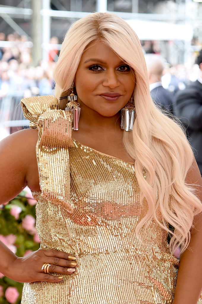 This year's Met Gala theme is Camp: Notes on Fashion, which basically means everyone in attendance has been encouraged to go completely over the top, and we haven't been disappointed. As much as it's about the gorgeous gowns and outrageous coats, Mindy Kaling reminded us that it's also about the hair as she debuted her platinum blond waves with subtle rose gold highlights, and we are in love with the Oceans 8 vibes it's giving us. Her long, golden hair is the perfect complement to her shimmery gold dress and absolutely embodies Camp. From Lady Gaga's mile-long eyelashes to Harry Styles's tribute to The Girl With the Pearl Earring, celebrities have truly taken the theme to heart this year. Keep reading to see Kaling's hair shine on the pink carpet.       Related:                                                                                                           Do Lady Gaga's Eyes Work Out? Because They Have to Be STRONG to Hold Up Those Lashes