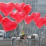 A woman fixes red heart-shaped balloons on a fence in Berlin.
