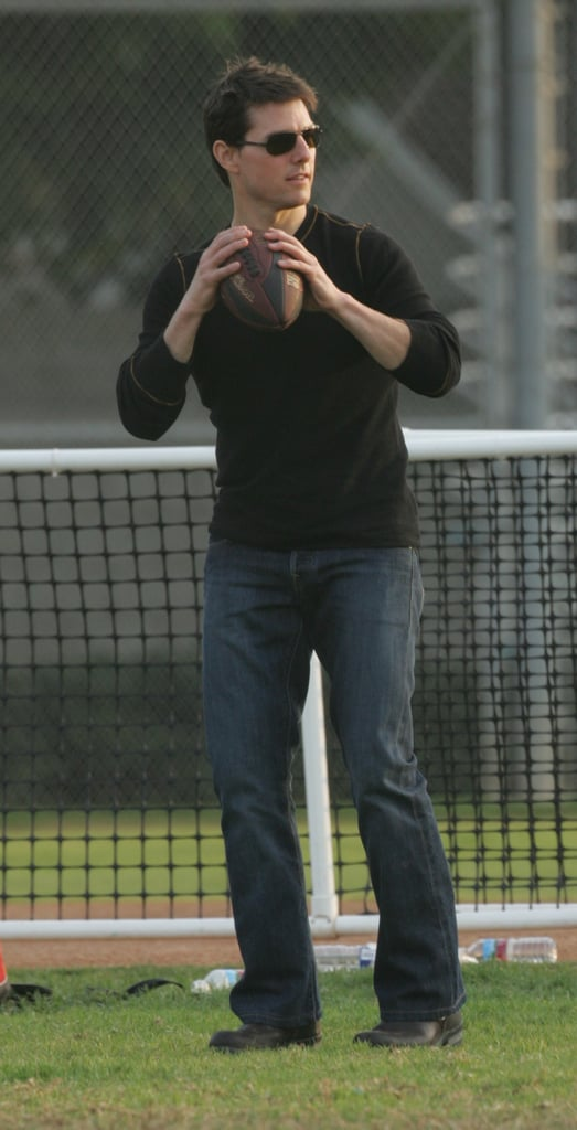 Tom Cruise got athletic to throw a football around while attending his daughter Isabella's soccer game in LA in November 2005.