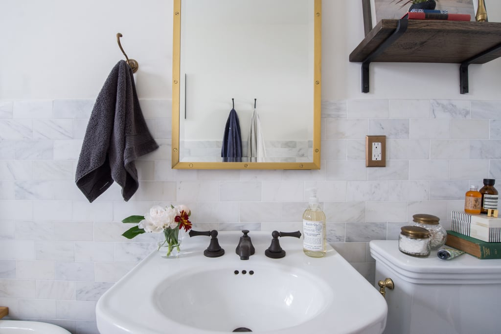 While brass details pair well with black and white, Sandie was careful not to over-do it. To keep it tasteful, she balanced the flashy brass with more subdued oil-rubbed fixtures on the sink.   Photo by Samantha Goh via Homepolish