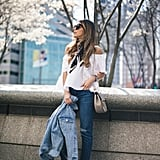An off-the-shoulder top with a silk scarf, skinny jeans, lace-up sandals, and a denim jacket.