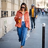 Style a white tank with wide-leg jeans and an orange jacket.