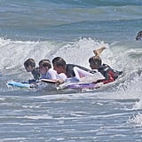 The Beckhams formed a tight pod and rode a wave back to the beach.
