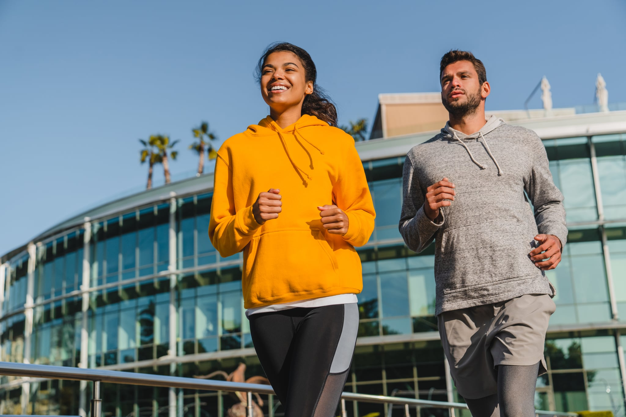Happy young mixed race couple jogging in sporty outfit in urban area