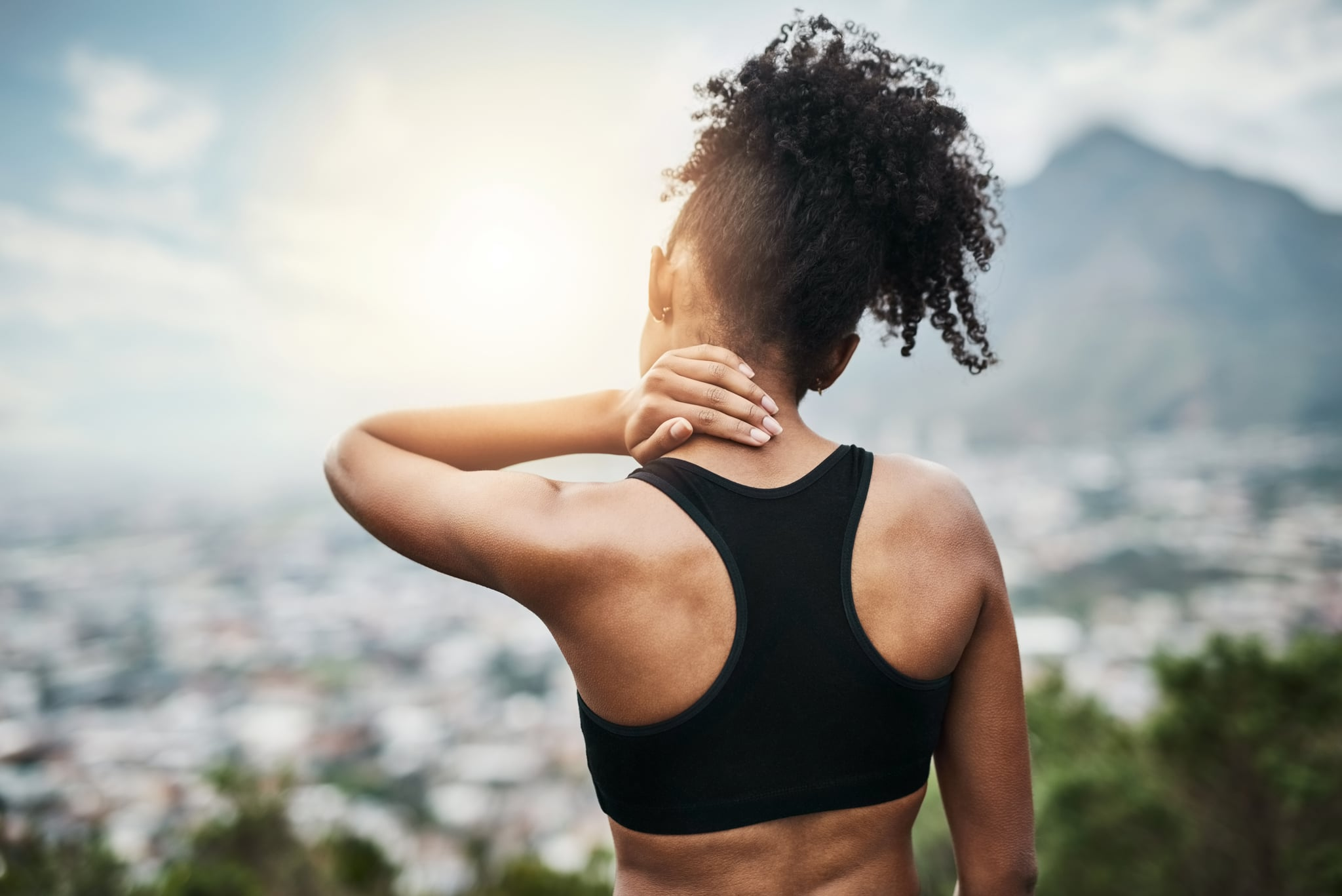 Rearview shot of a sporty young woman holding her neck while exercising outdoors