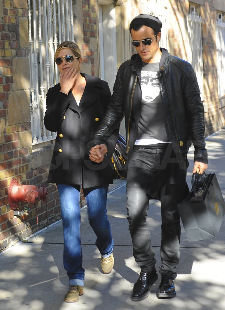 Jennifer Aniston and Justin Theroux hold hands near her NYC home.