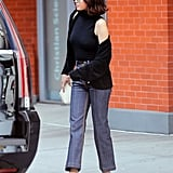 Selena styled a pair of patchwork Louis Vuitton jeans with a sleeveless turtleneck, a black cardigan, and Tod's loafers.