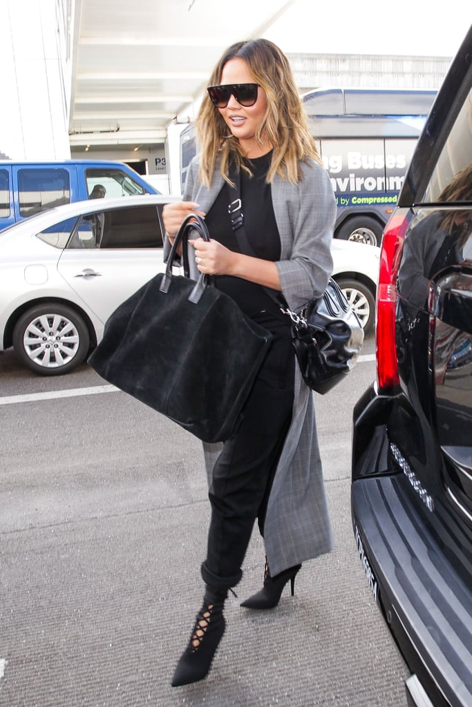 Chrissy wearing a chic tweed duster coat with a black shirt, matching jeans, and a pair of sexy lace-up boots.