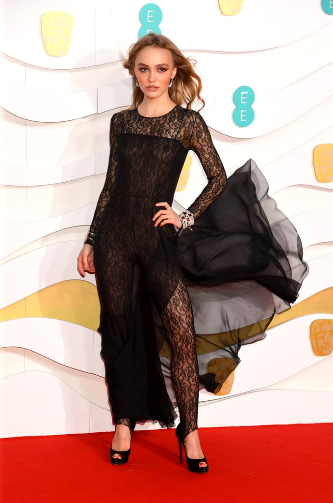 Lily-Rose Depp walked the red carpet on Sunday night for the 2020 BAFTAs, stunning in an all-black lacy look that gives new meaning to the naked dress. Her dress is from the Chanel Pre-Fall 2020 collection, and the supersexy look is one of the most showstopping ensembles of the night.  Lily-Rose's dress features a black lace catsuit layered under a sheer black spaghetti-strap dress, which features a ruffled hem and a thigh-high split. The sleeves of the bodysuit extend all the way to her wrists — where she's accessorized with Chanel chain bracelets that are embellished with rubies — and the leggings go past her ankles and hook underneath her simple black peep-toe heels.  Ahead, see Lily-Rose's gorgeous red-carpet look from all angles.