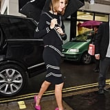 Taylor Swift shielded herself from the elements in London on Wednesday.