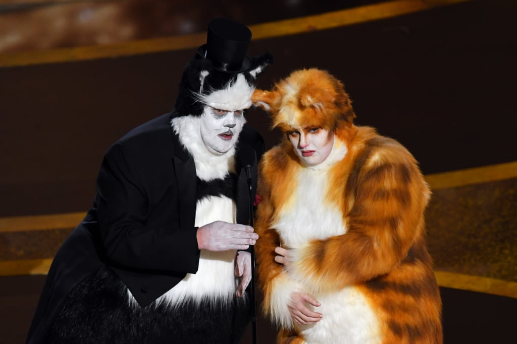 "Bustopher Jones and Jennyanydots — er, we mean James Corden and Rebel Wilson — put their best paws forward as they attended the Oscars on Sunday night. Though their film Cats received negative reviews from critics and failed at the box office, the costars proved they can laugh at themselves as they presented the award for best visual effects in furry costumes. ""As cast members of the motion picture Cats, nobody more than us understands the importance of good visual effects,"" they said. The sketch was clearly poking fun at their own film, which made headlines for its unfinished CGI and crazy visual effects. At one point, they even channeled their feline characters by hissing and clawing at the microphone. Whether you loved or hated Cats, you can't deny this skit was pretty purfect. See more pictures of their appearance ahead."