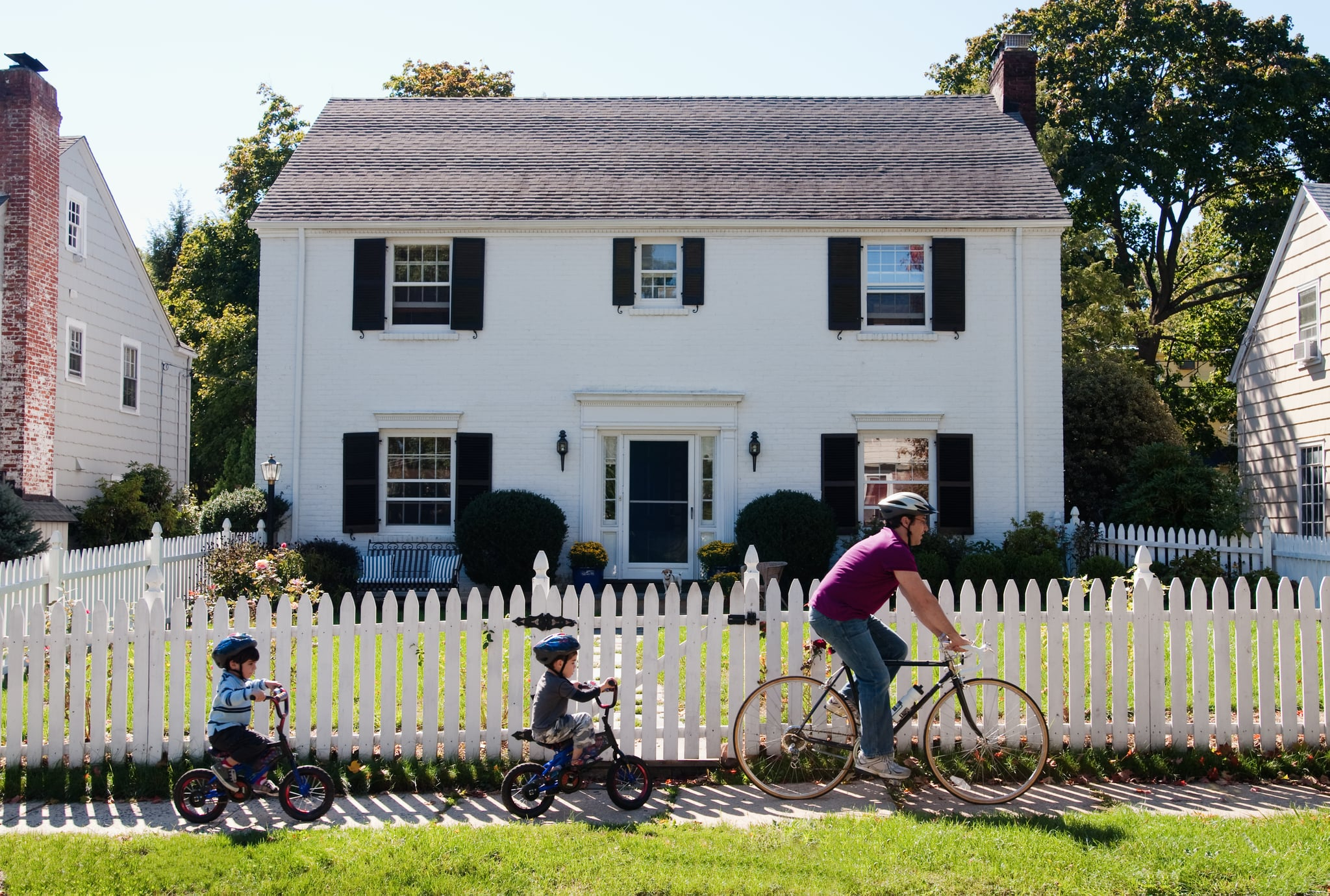 Father and twin 4-year-old sons riding bicycles in front of suburban home
