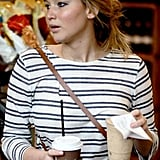 Jennifer Lawrence juggled two drinks in the checkout line.