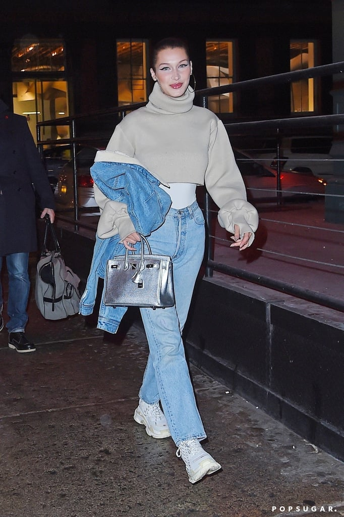 We're big believers that crop tops aren't reserved solely for Summer. It just takes a little extra effort to style them for Winter. Bella Hadid showed us one easy way to do this just by layering. The model was spotted in NYC wearing a cropped turtleneck sweater, and while she could have left it as just that, Bella expertly layered a white shirt (a bodysuit, perhaps?) underneath her top. Not only did that extra piece keep her warm, it added dimension to her street style look. The star kept the rest of her outfit casual with a pair of blue jeans and dad sneakers. A pop of metallic from her Saint Laurent bag provided that designer touch and it seemed Bella was even warm enough to slip off her shearling denim jacket. Bella's layering trick isn't hard to replicate, or even decipher, which is why every fashion girl should give this a try. If you feel inspired, shop similar cropped sweaters below and add your own layering twist.      Related:                                                                                                           Bella Hadid Couldn't Decide on an Outfit For a Basketball Game, So She Brought Them All
