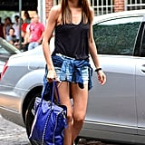 With a nod to grunge, Miranda outfitted a pair of cutoffs and a tank with tough-girl booties, a tied shirt around the waist, and a bright blue carryall.
