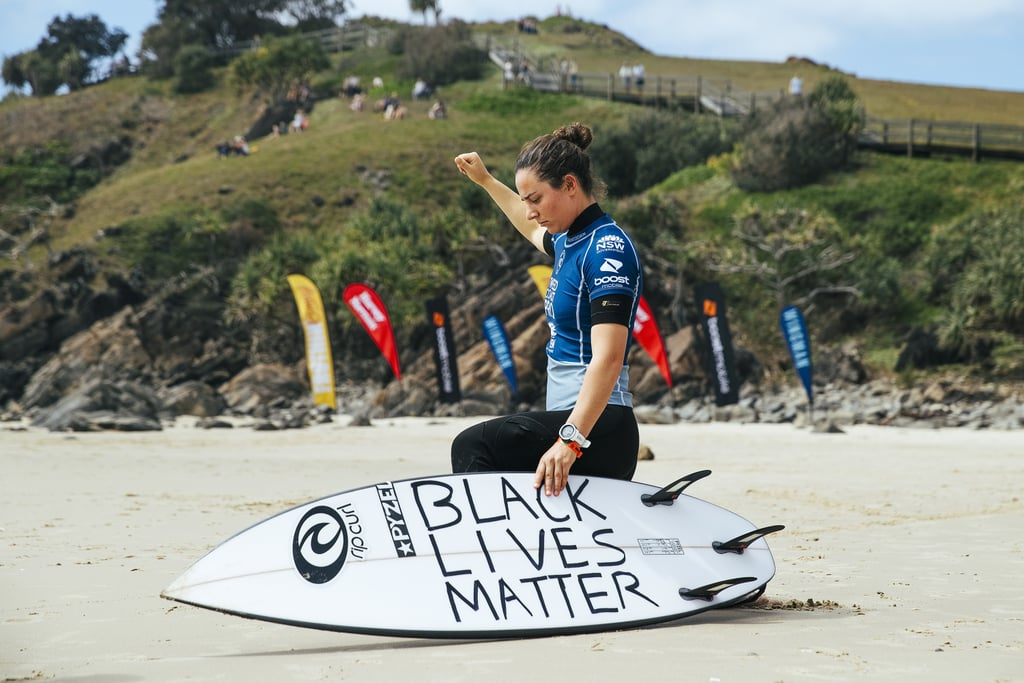 """Tyler Wright won the Tweed Coast Pro surfing event in Australia this weekend, but it's her actions on the sand that are really making waves. Wright, a two-time World Surf League champion from Australia, took a knee during her opening heat and propped up her surfboard to show the message on the bottom: """"Black Lives Matter."""" In an Instagram post, Wright expanded on her decision while acknowledging her privilege, both as a white woman and a professional athlete. """"These are divisive times and I'm a long way from perfect, but I deeply believe in the pursuit of racial justice and equality for everyone,"""" she wrote. """"I understand my white privilege and having this platform within the surfing community means I have the choice to say something and do something . . . and that many don't have that opportunity. I need to say more and do more with mine and I'm committed to challenging and changing the systems that continue to discriminate and oppress people of different backgrounds."""" Wright also explained the symbolism behind the length of time she took to kneel: 439 seconds. """"One second for every First Nations person in Australia who has lost their life in police custody since 1991,"""" she wrote. In Australia, Indigenous people are incarcerated at four times the rate of Black people in the US, according to the BBC, and while they make up less than three percent of the nation, Indigenous people comprise a full 30 percent of the incarcerated population. The inaccessibility of data makes it difficult to pinpoint the number of Indigenous deaths in custody, but an analysis by The Guardian sets it at over 400 since 1991. The lack of consequences — no police officer has ever been held criminally responsible for an Indigenous death in custody in Australia — has led to outrage and protests across the country this summer. As Wright adds her voice to the fight, she's already faced backlash from the surfing community, which is historically exclusionary. At the same time, her decision has also"""