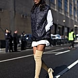 Wear Your Thigh-High Boots With a Puffer Vest and Baseball Cap