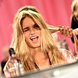 Romee Strijd winks coyly as she gets her strands touched up.