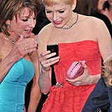 Michelle Williams checked out her phone with a friend.